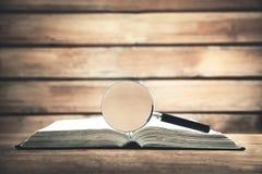 Lente d'ingrandimento con il libro sulla tavola di legno Cerchi e scopra immagine stock libera da diritti