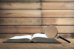Lente d'ingrandimento con il libro sulla tavola di legno Cerchi e scopra fotografia stock libera da diritti