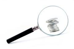 Lente d'ingrandimento con una colonna delle monete dietro Fotografie Stock Libere da Diritti
