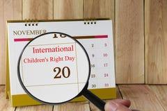 Lente d'ingrandimento a disposizione sul calendario che potete sembrare internazionale Immagini Stock