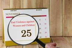Lente d'ingrandimento a disposizione sul calendario che potete sembrare internazionale Fotografia Stock