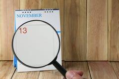 Lente d'ingrandimento a disposizione sul calendario potete guardare il giorno tredici o Fotografie Stock Libere da Diritti
