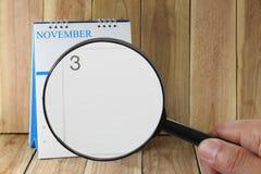 Lente d'ingrandimento a disposizione sul calendario potete guardare il terzo giorno della m. Fotografia Stock