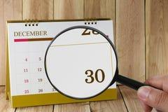Lente d'ingrandimento a disposizione sul calendario potete guardare la trentesima data Fotografie Stock Libere da Diritti