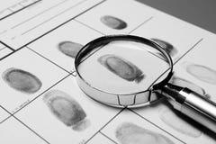 Lente d'ingrandimento e carta criminale dell'impronta digitale fotografia stock libera da diritti