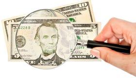 Lente d'ingrandimento e soldi Fotografia Stock