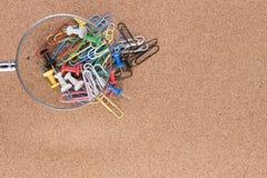 Lente d'ingrandimento sopra i paperclips ed i perni di disegno colourful Fotografie Stock