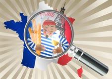 Lente d'ingrandimento sopra una mappa della Francia Uomo francese in berretto rosso con un bicchiere di vino Fotografie Stock Libere da Diritti