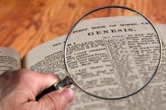 Lente d'ingrandimento su genesi famosa di capitolo della bibbia fotografia stock