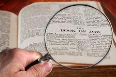 Lente d'ingrandimento sul capitolo famoso della bibbia del lavoro fotografia stock libera da diritti
