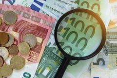Lente d'ingrandimento sul mucchio di euro banconote con le euro monete come fi Immagini Stock