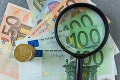 Lente d'ingrandimento sul mucchio di euro banconote e monete come affare Fotografia Stock Libera da Diritti