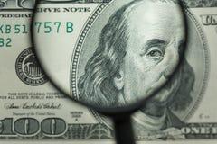 Lente d'ingrandimento sulla priorità bassa dei soldi Fotografia Stock
