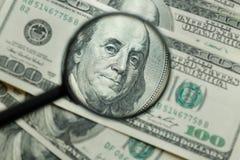 Lente d'ingrandimento sulla priorità bassa dei soldi Immagini Stock Libere da Diritti