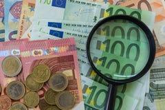lente d'ingrandimento sulle euro banconote con le euro monete come finanziarie Immagini Stock