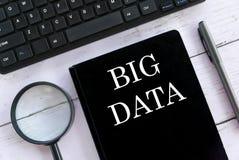 Lente d'ingrandimento, tastiera, penna e taccuino di vista superiore scritti con Big Data fotografie stock