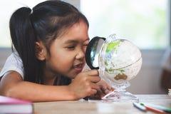 Lente de aumento asiática bonito do uso da menina da criança a olhar e estudar no globo imagens de stock royalty free