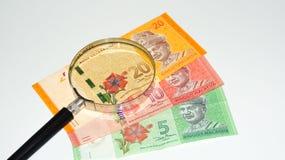 Lente de aumento com cédulas de Malásia Foto do conceito Foto de Stock Royalty Free