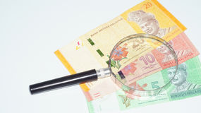 Lente de aumento com cédulas de Malásia Foto do conceito Imagem de Stock