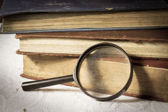 Lente de aumento com livros. fotos de stock royalty free