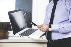 Lente de aumento da mão do homem com computador fotos de stock royalty free