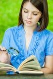 Lente de aumento do livro de leitura do close-up da jovem mulher Imagens de Stock