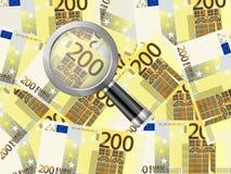 Lente de aumento em dois cem fundos do euro Foto de Stock Royalty Free