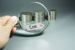 Lente de aumento, etiqueta do custo, e pilha de moedas no backdround Foto de Stock