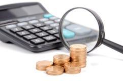 Lente de aumento, moedas e calculadora Imagem de Stock Royalty Free
