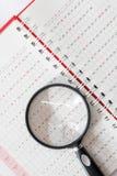 Lente de aumento na página do calendário do caderno Fotos de Stock