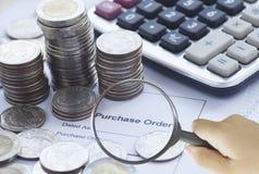 Lente de aumento que encontra a ordem de compra com as moedas da calculadora e do dinheiro Fotografia de Stock
