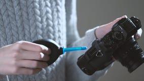 Lente de cámara de la limpieza del fotógrafo con un ventilador metrajes
