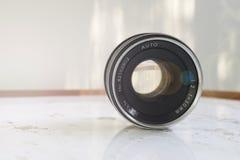 lente del vintage de 50m m con una llamarada y luces suaves en una tabla del grunge foto de archivo libre de regalías