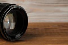 Lente della foto della macchina fotografica sulla vecchia tavola di legno fotografia stock