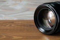 Lente della foto della macchina fotografica sulla vecchia tavola di legno immagine stock