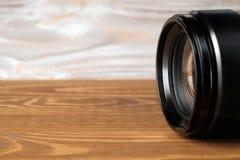 Lente della foto della macchina fotografica sulla vecchia tavola di legno immagini stock libere da diritti