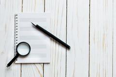 Lente e taccuino, penna su un contesto di legno bianco fotografia stock libera da diritti