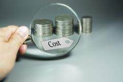 Lente, etichetta di costo e pila di monete nel backdround Fotografia Stock