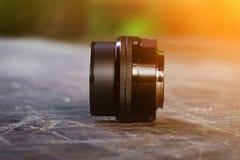 Lente per la macchina fotografica, su un vecchio scrittorio di legno, lente nera, fotografo fotografia stock