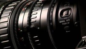Lente professionale della videocamera portatile su fondo scuro, macro