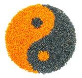 Lenteja anaranjada y negra que forma un símbolo de yang del yin fotografía de archivo