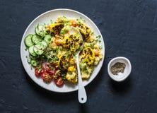 Lentejas amarillas, calabaza, coliflor asada de la cúrcuma y verduras en un cuenco - comida vegetariana sana en un fondo oscuro, foto de archivo libre de regalías