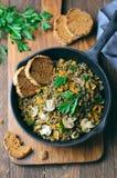 Lentejas con las setas, la zanahoria y las hierbas en una sartén, comida vegetariana sana imagen de archivo