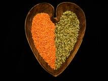 Lentejas rojas y verdes en un cuenco de madera en forma de corazón Foto de archivo