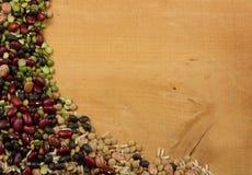 Lentejas y arroz clasificados de las habas en un tablón Imágenes de archivo libres de regalías