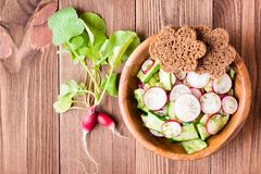 Lenten spring vegetable salad of cucumber, radish, greens. And rye bread  in a plate on a wooden table. Top view Stock Photo