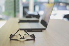 lentes, bolígrafo, ordenador, cuaderno en el escritorio de oficina megabus imagen de archivo libre de regalías