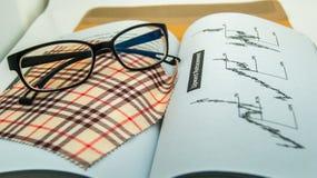 Lentes con el libro del análisis del técnico Foto de archivo