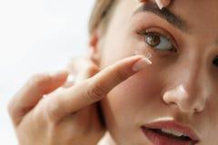 Lentes de contato da visão Close up com a cara bonita da mulher fotografia de stock royalty free