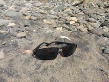 lentes de la lente en la arena del r?o imágenes de archivo libres de regalías